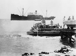 Lightering - In May 1935, Pan American Airways (PAA) construction workers use a barge to lighter building materials from the SS North Haven to the dock at Wilkes Island, Wake Atoll.