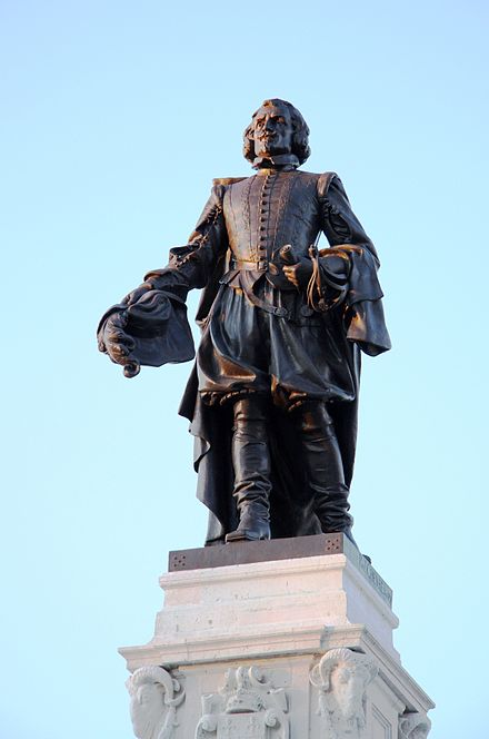 Statue of Samuel de Champlain at sunrise (looking to the north-west; with a similar expressive face as traditionally Jacques Cartier's), by Paul-Romain Marie Léonce Chevré [fr] (Paris, 1896–1898), as newly repaired for 2008, at Quebec City since 1898, near Château Frontenac grand hotel, on the Terrasse Dufferin.