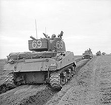 A column of tanks advance from the left to right, each tank following in the preceding tanks track marks.