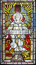"The image on the glass is of an angel in full frontal with wings outstretched behind and above holding a banner that reads ""Praise Ye the Lord"""