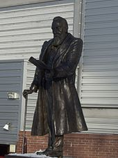 A bronze statue of a man with a large beard, wearing a long coat, leaning on a walking stick, and holding some papers