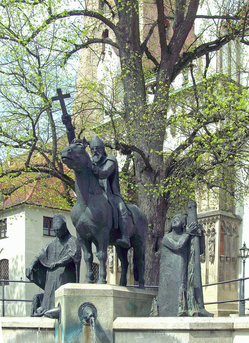 Biskop Ulrik til hest på Lechfeld, statue mellom de to andre hellige fra Augsburg, Afra og Simbert, foran domkirken i Augsburg