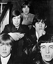 Black-and-white photograph of The Rolling Stones sitting on a staircase in 1965.