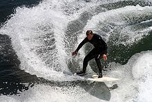 Photo of surfer wearing wetsuit catching wave