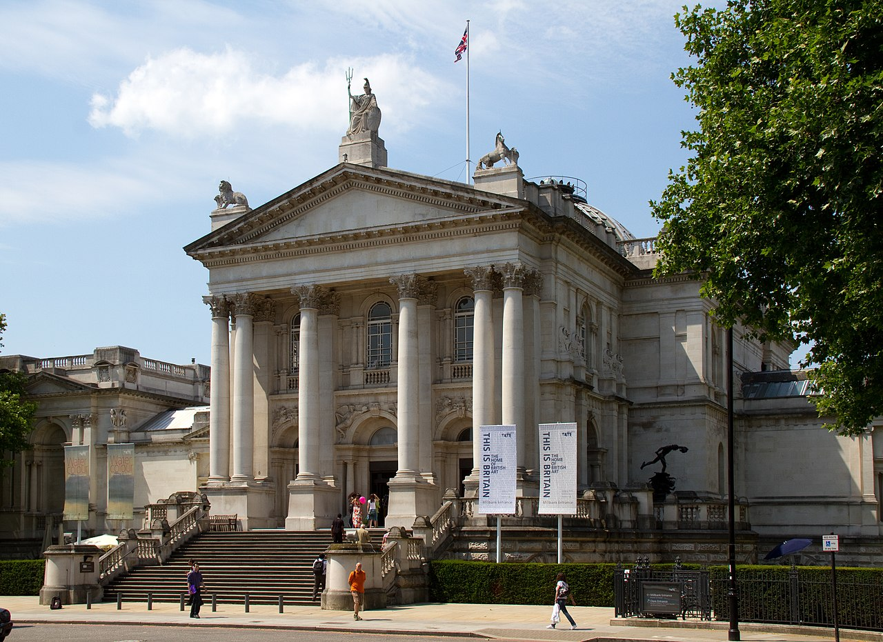 image of the front of the Tate Britain gallery: it is a large neo-classical building in limestone with a portico bearing several columns