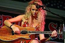 Taylor Swift sits and leans over her oak guitar while picking a string