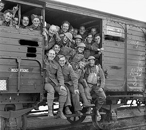 "Forty-and-eights - British soldiers on board a quarante et huit wagon in France in 1939. The stencilled sign in the top right of the picture says ""HOMMES 40 : CHEVEAUX (en long) 8"". The shared experience among Allied soldiers spawned groups such as the Forty and Eight veterans organization."