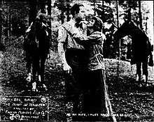 An old photo showing a woman embracing a man in front of two horses