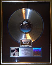 A silver-colored gramophone record displayed in a frame behind glass.