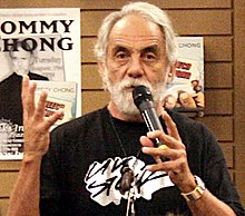 "A well-tanned man with white hair and a white beard holds a microphone in front of his face. On his left wrist, he wears a heavy silver-colored watch; with his right hand, he is gesturing. On the wall behind him are two signs: one bears the name ""Tommy Chong""."