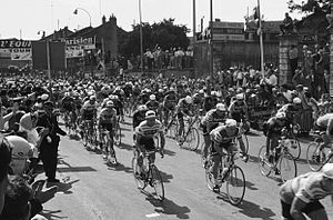 A black and white photograph of a large group of cyclists riding under a starting banner.