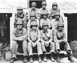 Black-and-white photo of eleven Marines in their combat uniforms sitting on some stairs