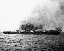D'énormes colonnes de fumée s'élèvent d'un porte-avions fortement incliné sur tribord. Plusieurs foyers d'incendie sont clairement visibles sur l'ensemble du navire.