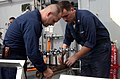 US Navy 050105-N-4383M-039 Hull Maintenance Technician 1st Class Jason Curry, left, and Hull Maintenance Technician 3rd Class Branden Stone, prepare to test a fresh water distribution manifold.jpg
