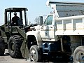 US Navy 050911-N-9712C-006 U.S. Navy Chief Equipment Operator Thomas Rolls, assigned to Naval Mobile Construction Battalion Four Zero (NMCB-40), moves a disabled dump truck out of the way with a front-end loader.jpg