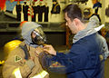 US Navy 060422-N-6823C-011 Personnel Specialist Seaman Scott Carroll helps a Navy Reservist dress out in fire fighting equipment during a general quarters exercise.jpg