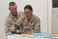US Navy 070303-M-6339F-009 Sailors help themselves to birthday cake at Hope Chapel in honor of the Seabee's 65th birthday.jpg