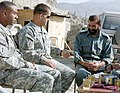 US Navy 071110-M-9719V-014 Sgt. 1st Class Willie Royal, left, and Army Capt. Francisco J. Miranda sit for a discussion and chai (Afghan tea) with Afghan National Police Maj. Badshah Wazir, the Shamal District police chief, duri.jpg