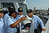 US Navy 080805-N-3885H-002 Boatswain's Mate 2nd Class Takesha Brown, left, assigned to Pre-Commissioning Unit (PCU) George H.W. Bush (CVN 77), shows fellow crew members Seaman Recruit Frank Lopez, center, and Seaman Recruit Rau.jpg
