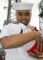 US Navy 081219-N-9758L-125 Electrician's Mate 1st Class Rafael Martinez greets his newborn child during the return of USS Reuben James (FFG 57) at Naval Station Pearl Harbor.jpg