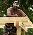 US Navy 090613-N-9968P-015 Builder 1st Class Dwayne Brown marks the placement of wood slats on a piece of playground equipment.jpg