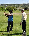 US Navy 101014-N-8241M-016 Professional golfer Jon Fine helps service members at Naval Station Guantanamo Bay Cuba with their golf game.jpg