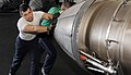 US Navy 101024-N-5361G-003 Aviation Machinist's Mate 3rd Class Jairo Brinas, from Roselle, Ill., pushes an aircraft engine into position for instal.jpg