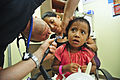 US Navy 110712-N-ZZ999-018 Lt. Cmdr. Cory Russell examines the ear canal of a Micronesian girl.jpg