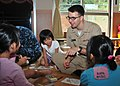 US Navy 111006-N-CG241-090 Ensign Jerome Benson colors artwork with children during a community service project.jpg