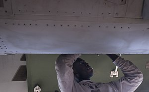 US Navy 120107-N-TZ605-095 Aviation Electronics Technician 2nd Class Attah Anoh, assigned to Strike Fighter Squadron (VFA) 81, performs maintenance.jpg