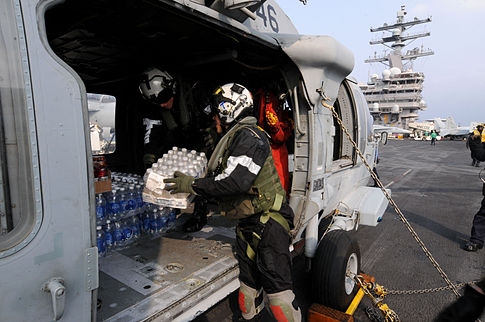U.S. Navy sailors transfer humanitarian supplies from an aircraft carrier to a helicopter. Image: U.S. Navy.