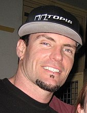 Head shot of Vanilla Ice with a goatee wearing a black T-shirt and baseball cap.
