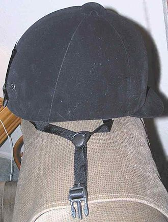 Equestrian helmet - A modern ASTM/SEI show-legal helmet covered in velveteen to resemble the old style hunt cap, but has visibly more protective material and an attached harness