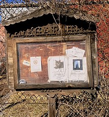 "Wooden notice board labeled ""Vinegar Hill"", with several flyers for community events under glass."