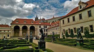 Un jardin à la française, orné de statues, entouré par plusieurs corps de bâtiments Renaissance, en pierre de taille claire, aux toits de tuiles. La cathédrale sur une hauteur à l'arrière plan.
