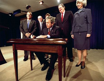 Underwood (far left) stands by President George W. Bush and other dignitaries for the signing of a bill. Wetlands-conservation-act.jpg