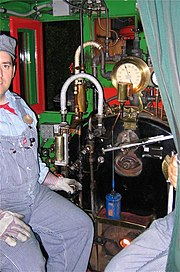 A smiling fireman sitting inside the locomotive's cab next to an assortment of valves, levers, and gauges