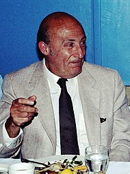 An bald elderly man in a suit and tie, seated before a meal, raising his right hand slightly and look to the right of the picture.