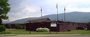 The reconstructed fort is a wooden log construction, painted brown, roughly a single story tall. There are four flagpoles, from which fly a variety of flags, including the American flag and a British Union Jack.  Mountains are visible in the background.