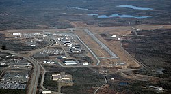 An aerial photo of an airport surrounded by forest.
