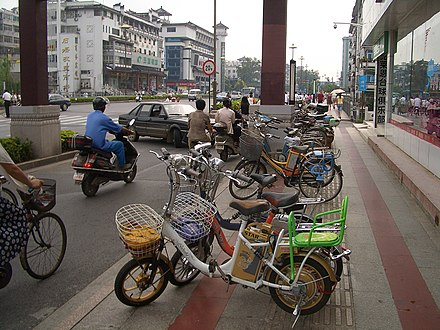 Electric bicycles parked in Yangzhou's main street, Wenchang Lu. They are a very common way of transport in this city, in some areas almost outnumbering regular bicyles Yangzhou-WenchangLu-electric-bicycles-3278.jpg