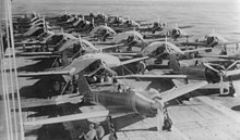 Environ trente appareils, dont certains sont bâchés, se trouvent sur le pont d'un porte-avions. Des personnels au sol sont assis à l'ombre des ailes.