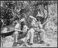 """Marine Sgt. F. Smit...and Cpl. S. Brown...open a coconut to get a cool drink on Saipan."", 06-1944 - NARA - 532391.tif"