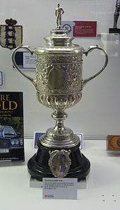 A trophy, silver in colour and topped by a figure of a footballer, on an ebony plinth