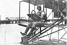 photo of Cunningham sitting in a biplane trainer