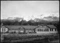 A low-lying mountain lodge, at the foot of snow-covered hills. ATLIB 294484.png