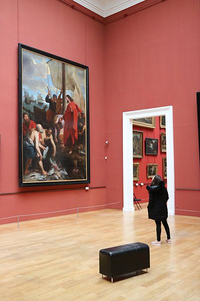 File:A woman contemplating an artwork in the pink room next to a bench.jpg