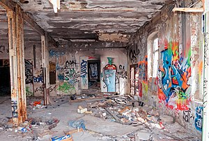 Photograph of the inside of an abandoned building with prolific graffiti covering the walls