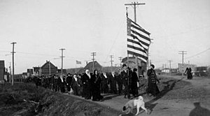 Ahmeek, Michigan - A parade of strikers headed by women of the Western Federation of Miners parade on a morning in October 1913 in Ahmeek, Michigan. It wasn't uncommon to have women and children at the front of such parades.