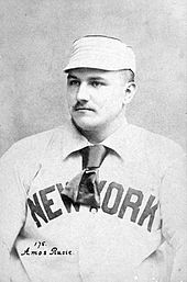 "A seated man in a white baseball cap and white baseball uniform shown from the chest up. He is looking to the left of the image. He has a small mustache, and his jersey reads ""NEW YORK"" in dark block type, partially obscured by a short tie worn around his neck under the collar of his jersey."
